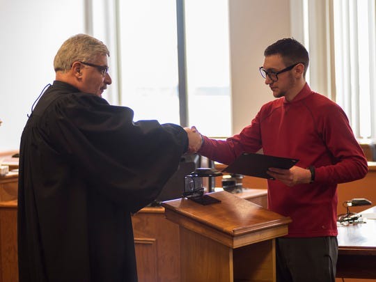 St. Clair County Probate Judge John Tomlinson, left, shakes hands with Travis Armstrong during the Adult Mental Health Court graduation ceremony Tuesday, April 17, in Judge Tomlinson's courtroom. For completing the program, Armstrong was given a certificate of completion and a gift card.