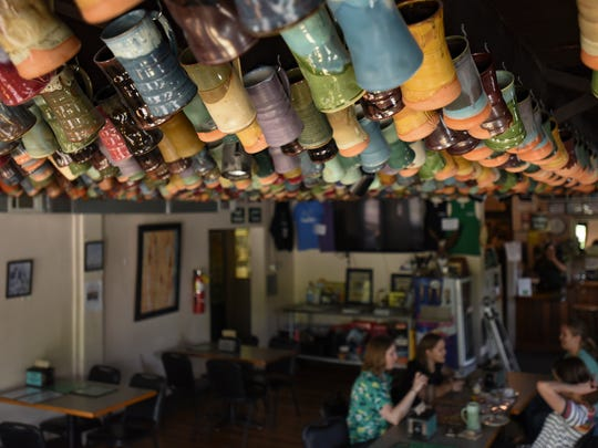 A bevy of handcrafted Mug Club mugs made locally hang on the ceiling of EagleMonk Pub & Brewery in Delta Township.