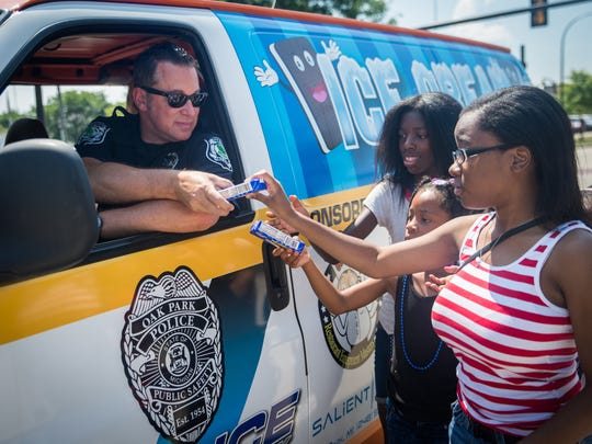 Robert Koch, Community Resource Officer for the Oak Park Police Department, hands out ice cream to children during the annual Independence Day Parade in Oak Park on Wednesday, July 4, 2018.