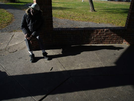 The shadow of 67 year-old Leander Gardner cast across the concrete where he slept underneath a pavilion in Kirkwood Park last Thanksgiving when he was homeless. Gardner now lives a block away from the park where he is a resident at Sacred Heart Village II.