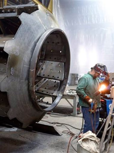 In this photo taken on Thursday, Feb. 12, 2015, a man welds parts in fans for industrial ventilation systems at the Robinson Fans Inc. plant in Harmony, Pa. The Commerce Department says the gross domestic product, the economy's total output of goods and services, expanded at a 2.3 percent annual rate in the second quarter, up from a 0.6 percent first quarter increase. The first quarter figure was revised from a previous estimate of a 0.2 percent decline.
