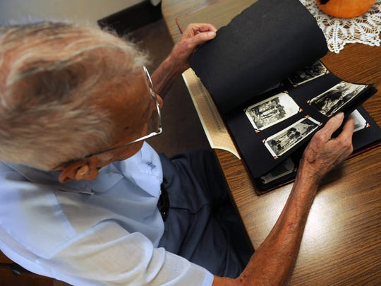 World War II veteran Harold Smith of Duncan Falls looks through a photo album filled with images from his time in service.