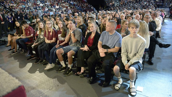 In this Wednesday, Feb. 21, 2018, file photo, Marjory Stoneman Douglas High School students and parents wait for a CNN town hall broadcast to begin at the BB&T Center in Sunrise, Fla.