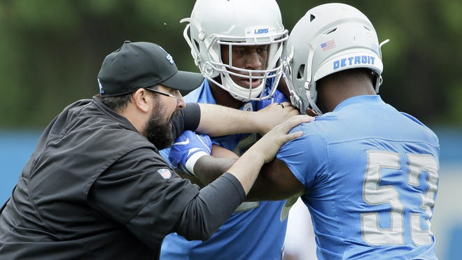 FILE - In this June 6, 2019, file photo, Detroit Lions coach Matt Patricia, left, works with linebackers Tre Lamar, center, and Malik Carney (53) during NFL football training camp in Allen Park, Mich.