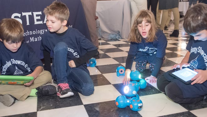First-graders Nicolas Kovacheff Badke and Chloe David, and second-graders Amber Hieb and Nathan Dahl put their robots, Dash and Dot, through their paces.