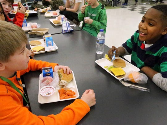 Third-graders Caleb Toler, left, and Titus Taylor eat their school lunches in the cafeteria at Buchanan Elementary school Thursday, Feb. 18, 2016.