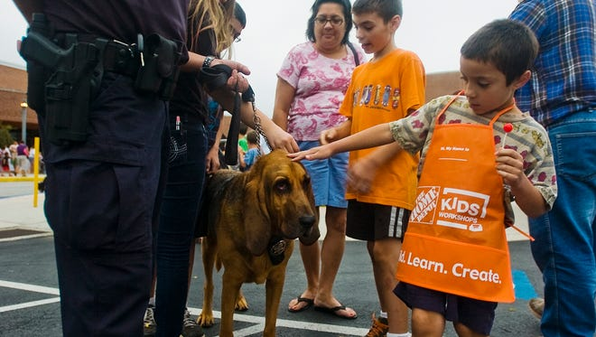 Mark Keating, 7, of Hanover pets York County Sheriff's Office K-9, Lou during a National Night Out event hosted by Penn Township Police Department in 2013. This year's Night Out event has been canceled.
