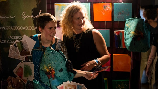 Grace Goad, left, and her mother Leisa Hammett display Goad's art at a recent art show.