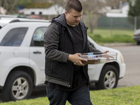 Scott Mills, left, delivers a prepared meal Thursday.