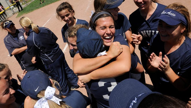 Granville senior pitcher Abby Barker hugs junior shortstop Shelby Sprouse in the center of a team huddle after Granville defeated Lakewood 2-1 in the Division II state softball championship on Saturday, June 6, 2015, at Firestone Park Stadium.