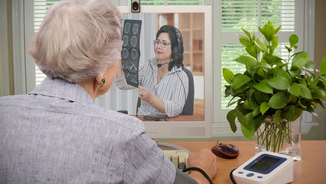In this stock image, a woman sits in front of a computer monitor after sending her blood pressure and pulse information to a virtual doctor, seen on the screen. At the same time, the telemedicine physician is looking at the woman's CT X-ray.