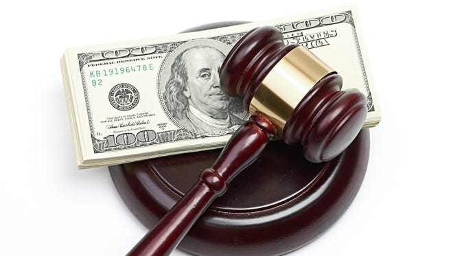 A file photo showing a court gavel on a stack of money.