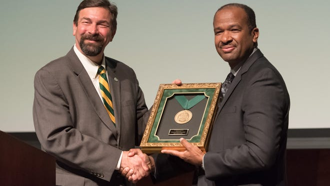 Colorado State University President Tony Frank presents the Founders Day Medallion to Eric Mosley, the son of honoree Lt. Col. John Mosley on Monday, Feb. 6, 2017.
