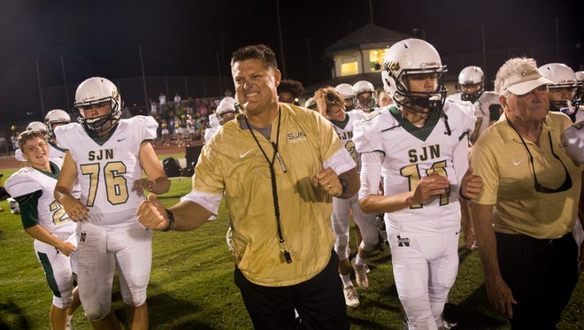 St. John Neumann head coach pumps his fist as he celebrates with his players shortly after defeating Community School of Naples, 27-13, to start 6-0 for the first time since football was reinstated at the school in 2001 Friday, October 20, 2017 in Naples.