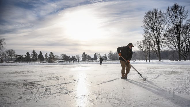 City of Mason facilities maintenance worker Pat Hicks, right, and Tom Silsby, the superintendent of the Department of Public Works smooth out areas of the rink at Rayner Park in Mason Thursday, Dec. 28, 2017.