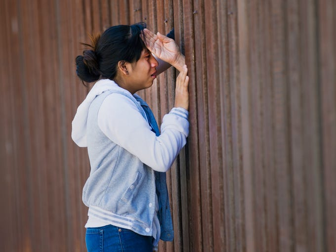 Fatima Rojas, 13 from Mesa, cries at the border fence