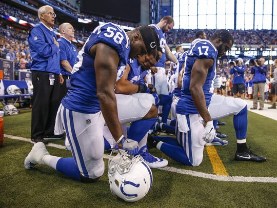 Colts teammates kneel together during the national