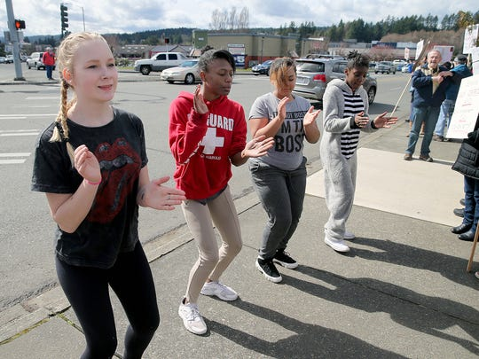 "Fairview Middle School drill team members perform at the Silverdale ""March For Our Lives"" protest Saturday.They are (from left) Emalee Kylven, 13, La'Asia Nesbitt, 12, Kylie Moniz , 13, and N'Dya Hudson, 12,."