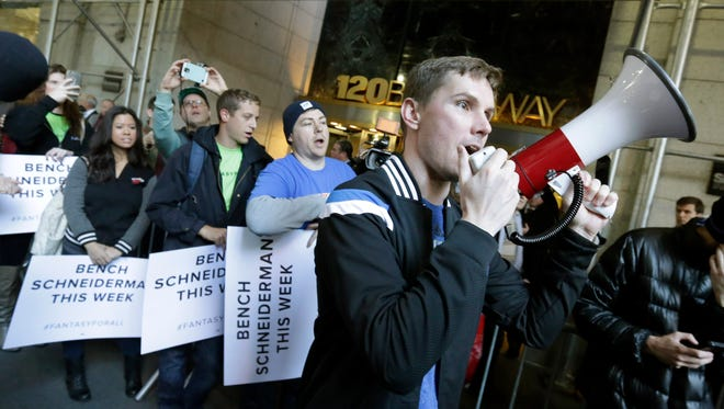 Geoff Bough, right, leads fantasy sports fans as they demonstrate outside the Financial District offices of New York state Attorney General Eric Schneiderman, in New York,