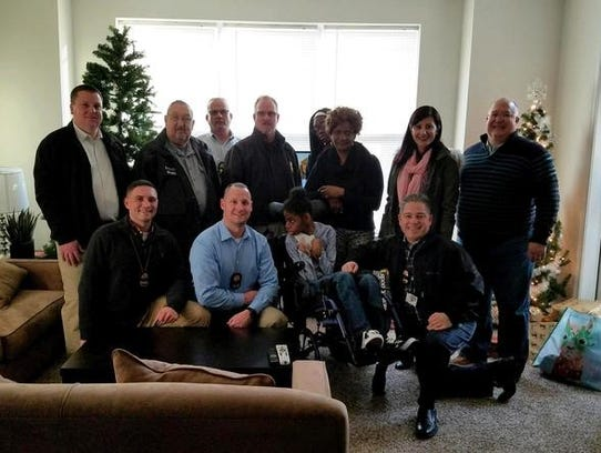 Members of the Maryland State Fire Marshal's Office and representatives of State Farm Insurance appear with the Pittman family, whom they've adopted for the holiday season after a fire displaced them from their Dawn Court home.