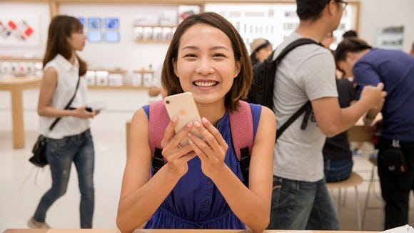 A woman holding an iPhone 8 inside of an Apple store.