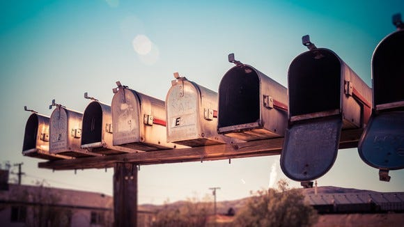 Row of mailboxes in a rural setting on a clear day.
