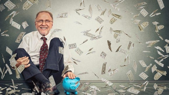 Older man sitting next to a piggy bank with money flying in the air around him.