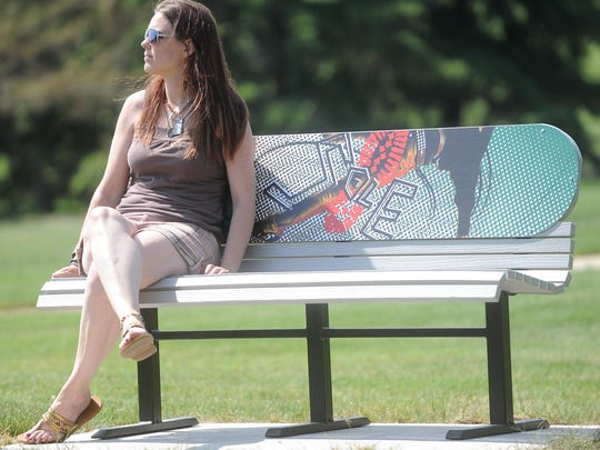 Blake Lieders' mother, Beata Lieders, sits on the new bench that carries a design created by her late son, at Adelaide Skate Park in Fond du Lac. The benches were donated by Interior Systems, Inc. of Fond du Lac.