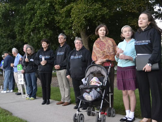 With her youngest daughter, 15-month-old Therese, in a stroller, Beth Mortensen of Green Bay stands next to her other two daughters - 14-year-old Marietta, far right, and 11-year-old Magdalena - and other participants during a candlelight vigil along South Webster Avenue at Baird Place Park in Green Bay for the 40 Days for Life fall campaign kickoff Wednesday night, Sept. 28.