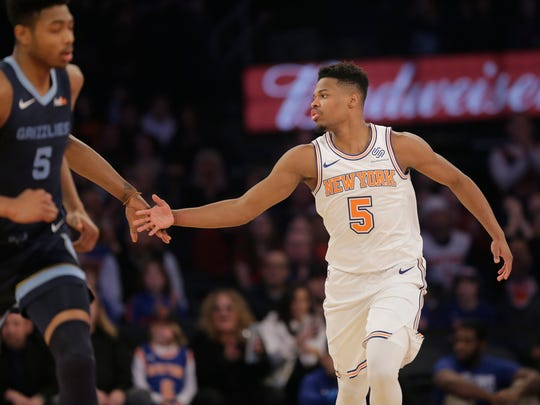 New York Knicks' Dennis Smith Jr., right, reacts after the Knicks scored during the first half of an NBA basketball game against the Memphis Grizzlies, Sunday, Feb. 3, 2019, in New York. (AP Photo/Seth Wenig)