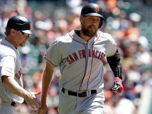 San Francisco Giants' Hunter Pence passes third base coach Phil Nevin after hitting a solo home run during the first inning of a baseball game against the Detroit Tigers, Tuesday, July 4, 2017, in Detroit. (AP Photo/Carlos Osorio)