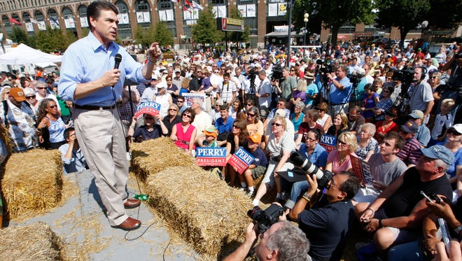 Texas Gov. Rick Perry chomps speaks to a large crowd at the Des Moines Register Soapbox at the 2011 Iowa State Fair.
