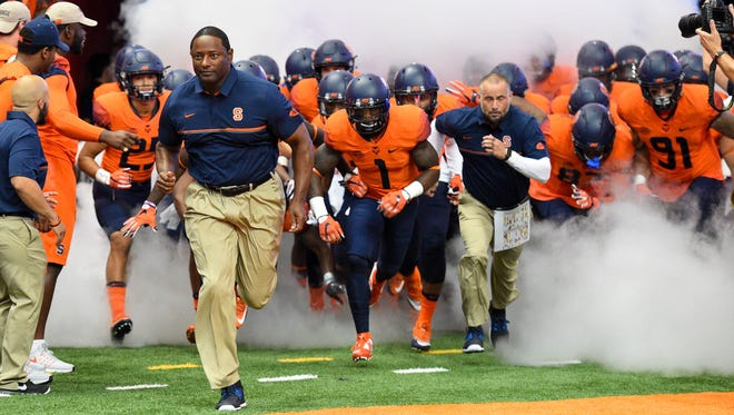 Syracuse Orange head coach Dino Babers leads his team on the field prior to the game.