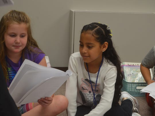 Makenna Meeks (left) and Hileana Gonzalez read their characters' parts of the Jack and the Beanstalk story at Hendersonville's SMORE Reading Camp July 2, 2018.