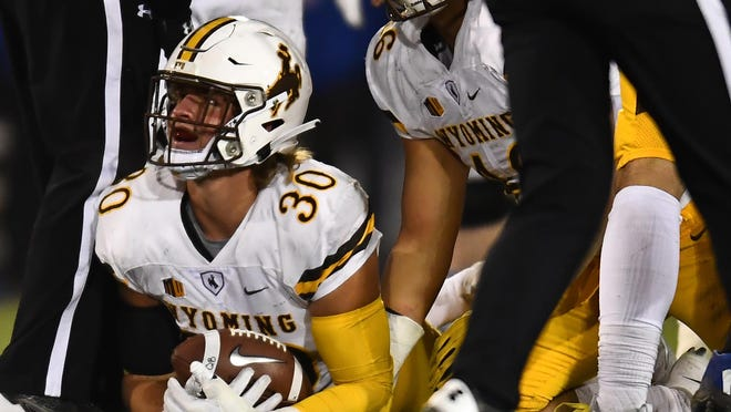 Nov 11, 2017; Colorado Springs, CO, USA; Wyoming Cowboys linebacker Logan Wilson (30) recovers a fumble in the second quarter against the Air Force Falcons at Falcon Stadium. Mandatory Credit: Ron Chenoy-USA TODAY Sports