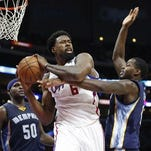 In this file photo, Los Angeles Clippers' DeAndre Jordan brings in a rebound in front of Memphis Grizzlies' Zach Randolph, left, and JaMychal Green, right, during the second half of an NBA basketball game in Los Angeles. DeAndre Jordan has chosen the Mavericks over the Los Angeles Clippers in what turned into a tense boom-or-bust wait for Dallas in pursuit of the free-agent center.