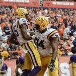 LSU wide receiver Malachi Dupre (15) celebrates his touchdown with teammate LSU offensive tackle Vadal Alexander (74) during the second half at Syracuse last month.