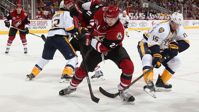 GLENDALE, AZ - DECEMBER 10:  Oliver Ekman-Larsson #23 of the Coyotes controls the puck under pressure from Craig Smith #15 of the Predators during the third period at Gila River Arena on December 10, 2016 in Glendale, Arizona. The Coyotes defeated the Predators 4-1.