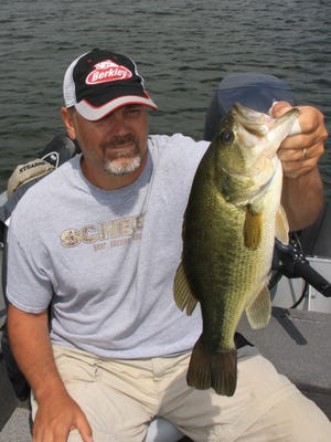 """Steve Taylor holds  big bass he caught while visiting a """"recycled"""" lake."""
