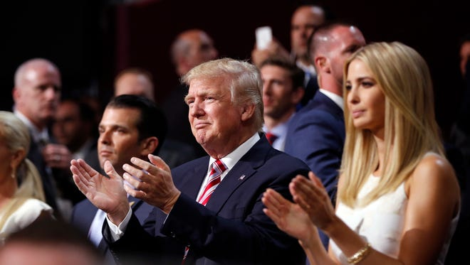 Republican Presidential Candidate Donald Trump, center applauds with Donald Trump, Jr., left, and Ivanka Trump as his son Eric Trump addresses the delegates during the third day session of the Republican National Convention in Cleveland, Wednesday, July 20, 2016.