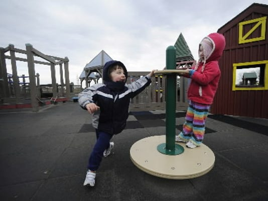 Then 4-year-old Brett Davis of Felton, left, and Josselyn Collier, then 3, of Dover  are bundled up as they play in February 2012 on the playground at Cousler Park in Manchester Township. Photo by York Daily Record/Sunday News -- Kate Penn.