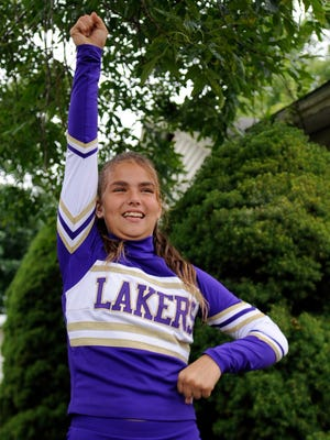Breanna Stoneburner practices a cheer Monday at her home in Thurston. Stoneburner and her family are raising money so she can perform in the All-American Cast for the Capital One Half Time show in Orlando, Fla., on Jan.1, 2015.