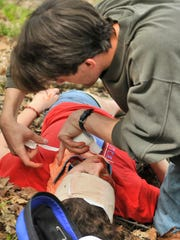 Junior Abraham Behr checks on junior Maria McGlinch during Wilderness Advanced First Aid training exercises Saturday.
