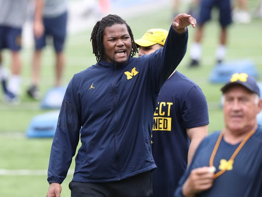 Michigan defensive lineman Rashan Gary works with high