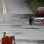 A man stands next to a car on a flooded street in Palm Harbor, Fla., Monday, Aug. 3, 2015.