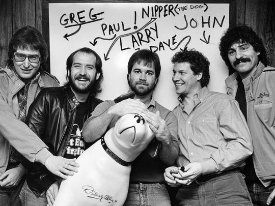 "The members of Restless Heart as a new group climbing the charts with their debut RCA single, ""Let the Heartache Ride,"" have a little fun with Nipper, the label's trademark March 5, 1985. They are Greg Jennings, left, Paul Gregg, Larry Stewart, Dave Innis and John Dittrich."