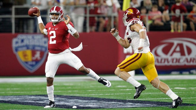 Alabama quarterback Jalen Hurts scrambles out of the pocket to throw a pass under pressure from Southern California defensive end Porter Gustin (45) during an NCAA college football game Saturday, Sept. 3, 2016, in Arlington, Texas.