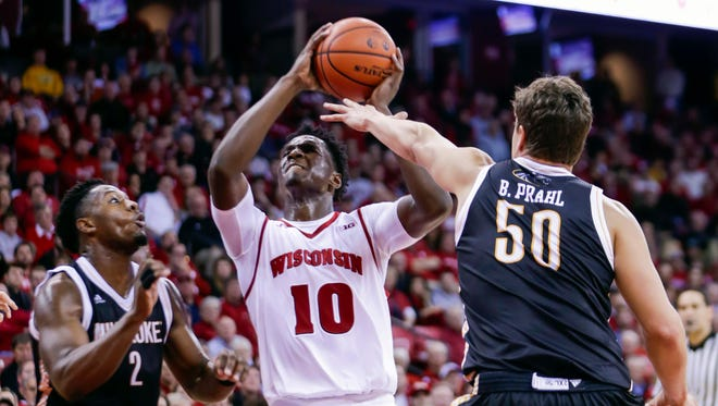 Wisconsin's Nigel Hayes (10) looks to shoot between Milwaukee's Akeem Springs (2) and Brett Prahl (50) during the second half of an NCAA college basketball game Wednesday in Madison. Milwaukee won 68-67.