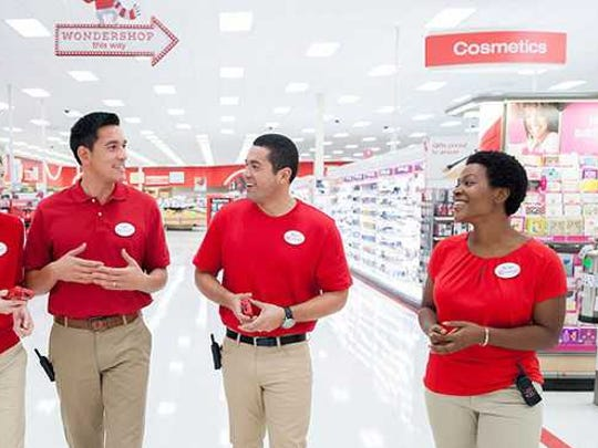 Target employees happily chat in an aisle.