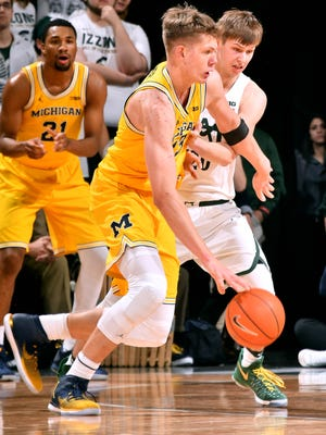 Spartan Matt McQuaid defends Wolverine Moritz Wagner as he moves the ball around the wing, while teammate Zak Irvin (21) hopes to get a pass.
